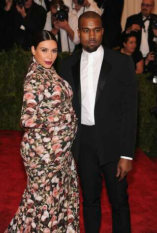 Kimye 2013: Designer darlings or fashion victims - or both? Each day seemed to bring a new bon mot or showy feud, a determinedly chic look or a high-profile wardrobe malfunction from exhaustively documented couple Kim Kardashian and Kanye West. Read more »  Pictured: A pregnant Kardashian in a less-than-flattering, form-fitting, floral-patterned maternity dress at the Met Gala. Photo: Jamie McCarthy