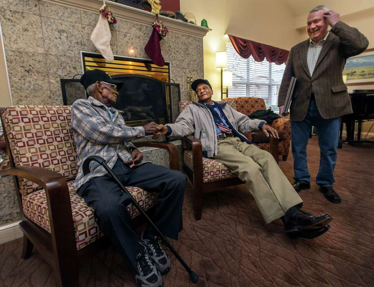 Richard Overton, 107, left, and Elmer Hill, 107, center, shake hands before Austin Texas Mayor Lee Leffingwell, right, presents a proclamation acknowledging and thanking Overton, and Hill for their service on Friday, Dec. 13, 2013, in Austin, Texas. Overton is Austin's oldest living World War II veteran and Hill is Henderson, Texas' oldest living World War II veteran. (AP Photo/Austin American-Statesman, Ricardo Brazziell) AUSTIN CHRONICLE OUT, COMMUNITY IMPACT OUT, MAGS OUT; NO SALES; INTERNET AND TV MUST CREDIT PHOTOGRAPHER AND STATESMAN.COM