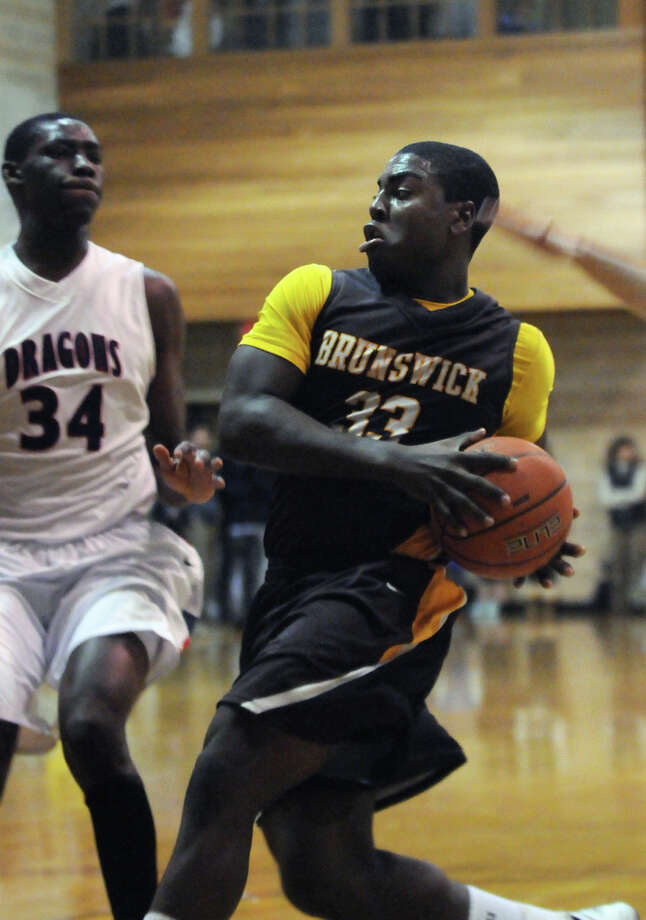 Brunswick's Dylan Wadsworth moves the ball as GFA's Sunday Okeke closes in as Brunswick hosts Greens Farm Academy in a boys basketball game in Greenwich, Conn., Dec. 13, 2013. Photo: Keelin Daly / Stamford Advocate Freelance