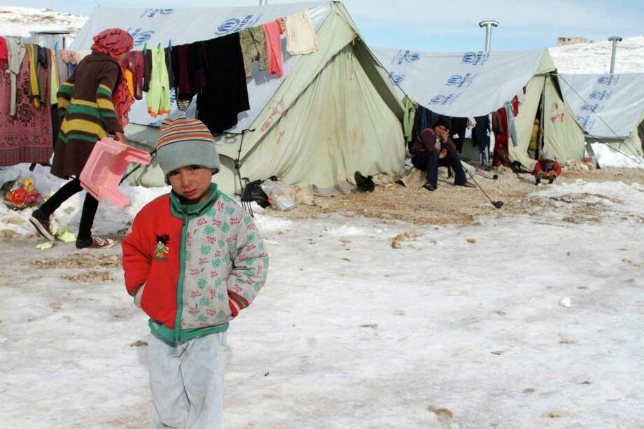 A Syrian child tries to keep warm Friday in a refugee camp in Lebanon. A snowstorm closed roads in Israel and gave Cairo its first snow in 100 years. Photo: -STR / AFP