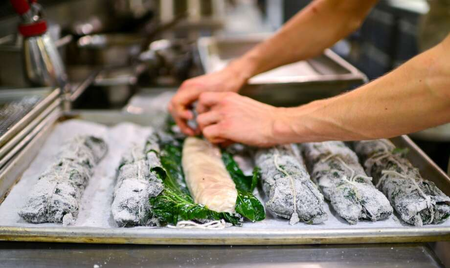 Sturgeon wrapped in collard greens, baked in ash, and served with potlicker, grits, and green tomato. Photo: Bonjwing Lee Photography