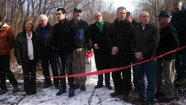 Brad Fischer, deputy Albany County executive, third from left, and Mark King, executive director of the Mohawk Hudson Land Conservancy, fifth from left, join elected officials who gathered with around 50 people on Saturday, Dec. 7, to cut the ribbon opening three miles of the Helderberg-Hudson Rail Trail between the intersection of Grove Street and Voorheesville Avenue in Voorheesville and Upper Font Grove Road in Slingerlands. With the 1.9 miles already open in Bethlehem, the trail has passed its halfway mark of completion between the Port of Albany and the village of Voorheesville. For information, visit mohawkhudson.org. (Submitted photo)