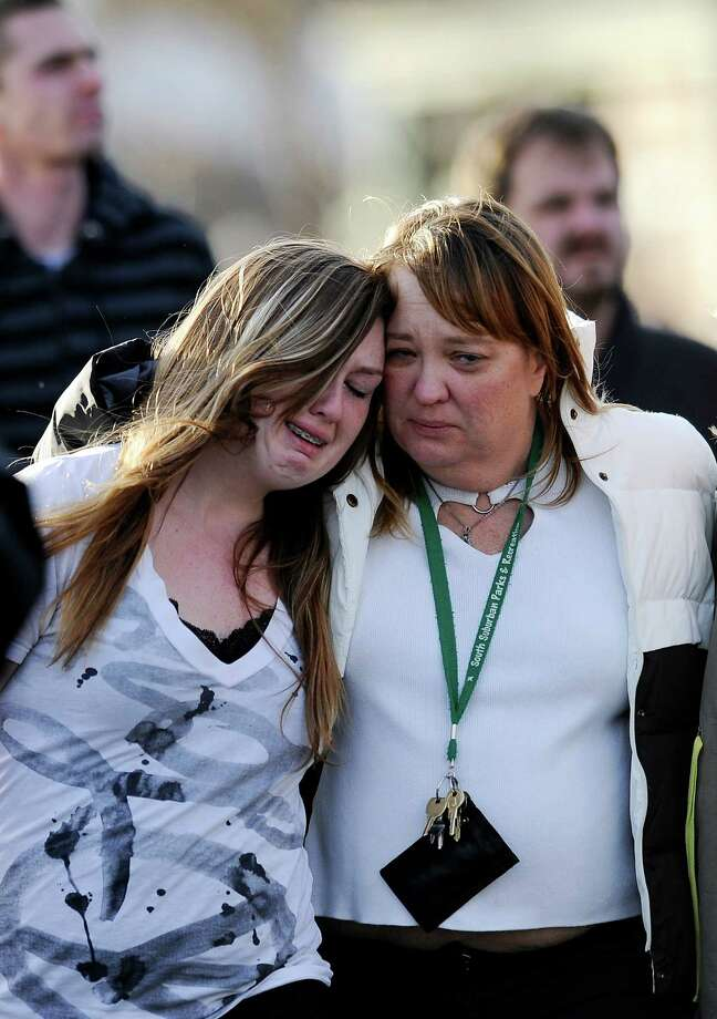 A parent escorts her daughter from nearby church grounds after a shooting on Friday at Arapahoe High School in Centennial, Colo. Police said they found a Molotov cocktail inside the school. Photo: Chris Schneider, Stringer / 2013 Getty Images