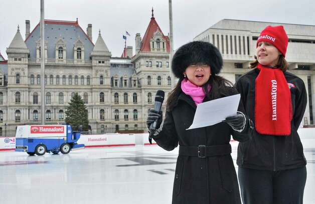 New York State Office of General Services special counsel to the commissioner Sabrina Ty, left, and Molly Tarleton of Hannaford Supermarkets  officially launch another season of skating against the backdrop of the State Capitol with the grand opening of the Empire State Plaza Ice Rink Friday Dec. 13, 2013, in Albany, NY.  Fridays will be Hannaford free skate rentals for the season.  (John Carl D'Annibale / Times Union) Photo: John Carl D'Annibale / 00025022A