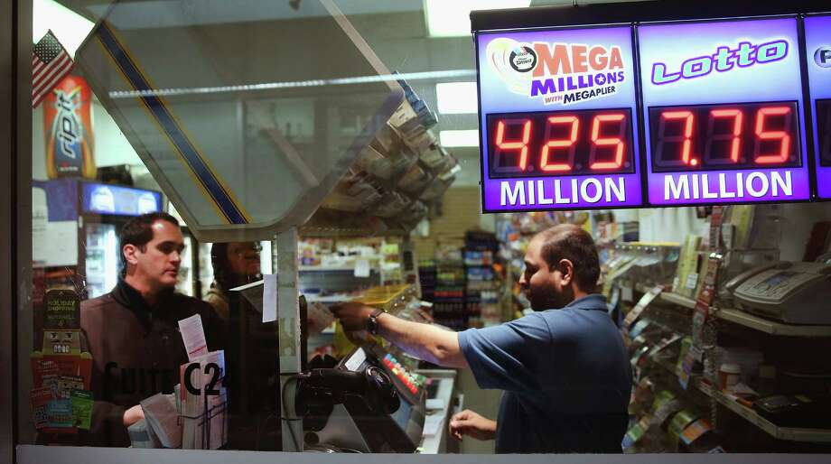 A clerk sells Mega Millions lottery tickets at a convenience store in Chicago. Friday's estimated $425 million jackpot was the second-largest jackpot in the history of the game. Photo: Scott Olson / Getty Images / 2013 Getty Images