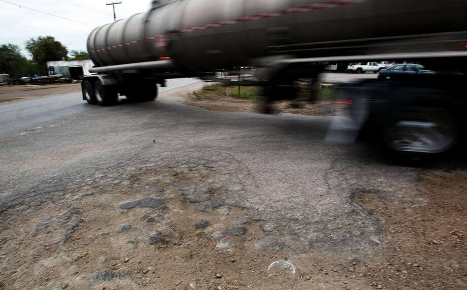 A tanker truck rolls past crumbling asphalt near Texas 119 and Texas 72 in Yorktown. Photo: John Davenport / San Antonio Express-News / SAN ANTONIO EXPRESS-NEWS
