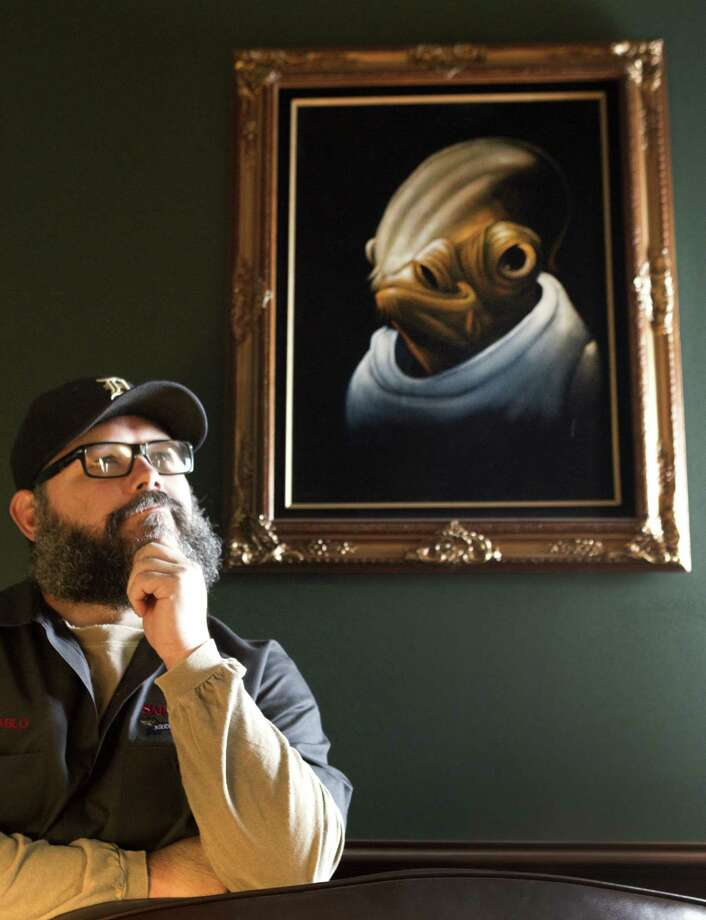 Brewer Vince Mandeville drew a high enough number in the white elephant gift exchange at Saint Arnold Brewing Co.'s Christmas party to steal the velvet painting he wanted from a co-worker. Photo: Brett Coomer / Houston Chronicle / © 2013 Houston Chronicle