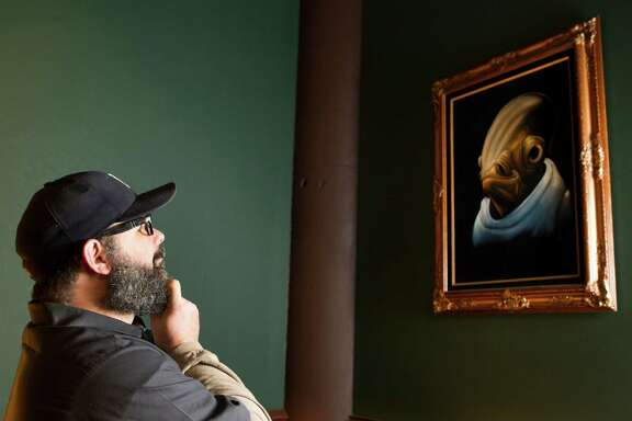 "Vince Mandeville, brewer at Saint Arnold Brewing Co., admires a velvet painting of ""Star Wars"" character Admiral Ackbar that he received as a White Elephant gift during a company Christmas party. And yes, he really wanted it."