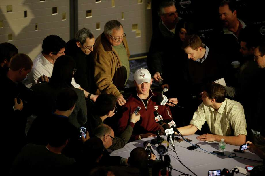 As a veteran of the Heisman Trophy festivities, a capped Johnny Manziel becomes the center of media attention Friday. But the Texas A&M quarterback doesn't expect to match last year's win, saying he voted for other finalists. Photo: Julio Cortez, STF / AP