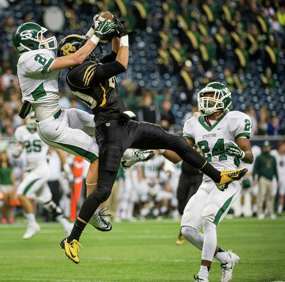 Brennan wide receiver Daniel Gonzalez (80) hauls in a pass as Stratford defensive back Greg Lee (2) defends during the first half of a class 4A state semifinal high school football playoff game at Reliant Stadium on Friday, Dec. 13, 2013, in Houston. Photo: Smiley N. Pool, Houston Chronicle / © 2013  Houston Chronicle