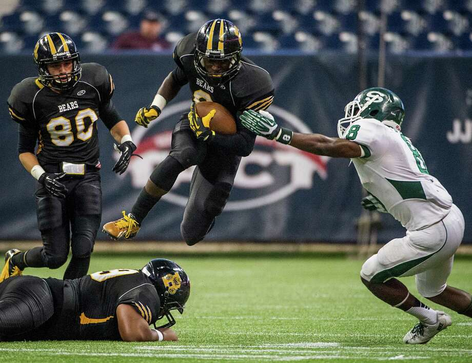 Brennan running back Nathaniel Wells Jr (8) leaps one of his own teammates as he tries to get past Stratford's Terrance Peters,Jr. during the first half of a class 4A state semifinal high school football playoff game at Reliant Stadium on Friday, Dec. 13, 2013, in Houston. Photo: Smiley N. Pool, Houston Chronicle / © 2013  Houston Chronicle