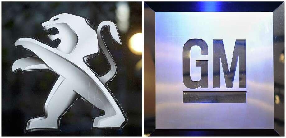PSA Peugeot Citroën, whose logo is at left, no longer has an alliance with General Motors. Photo: AFP, Staff / LIONEL BONAVENTURE