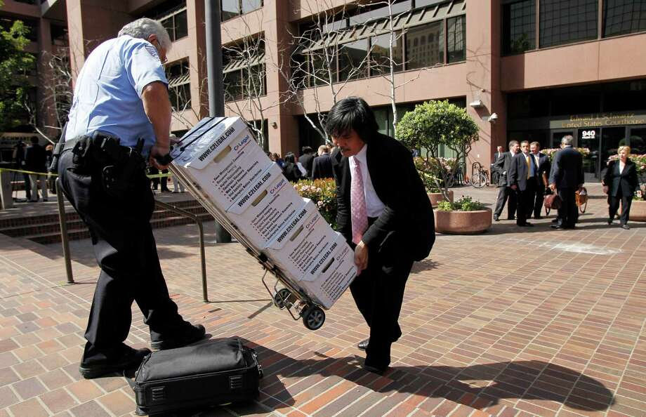 Documents on Toyota safety cases are carried into a courthouse in San Diego in 2010. After years of court battles over acceleration problems, Toyota agreed this week to enter talks to resolve hundreds of cases. Photo: Jae C. Hong, STF / AP