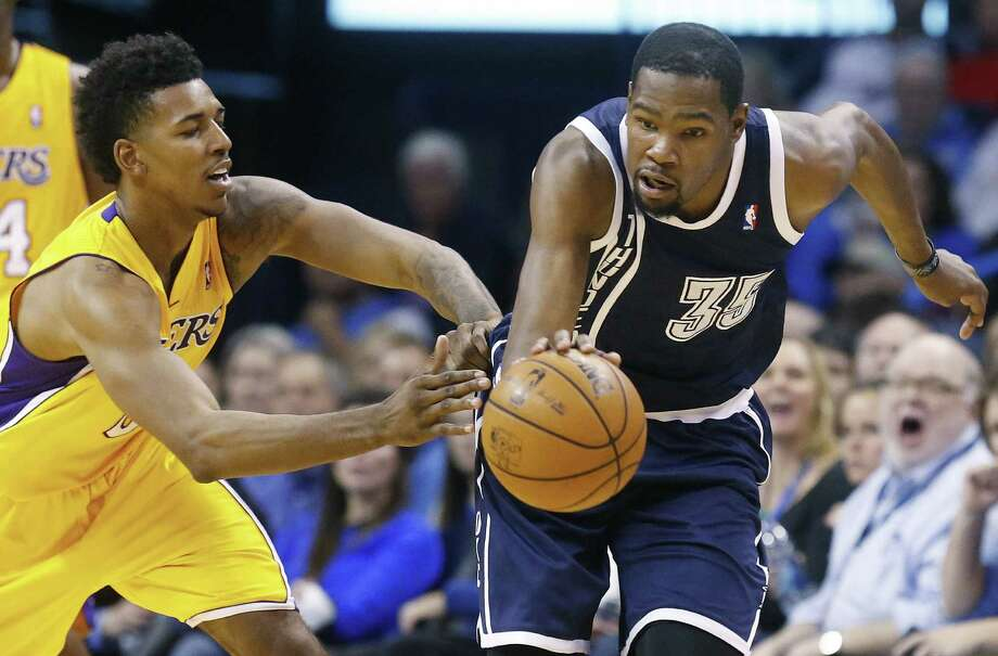 Oklahoma City's Kevin Durant (right) steals the ball from Los Angeles' Nick Young during the third quarter Friday. Durant scored 31 points for the Thunder, who have won 13 of their last 14 games. Photo: Sue Ogrocki / Associated Press / AP