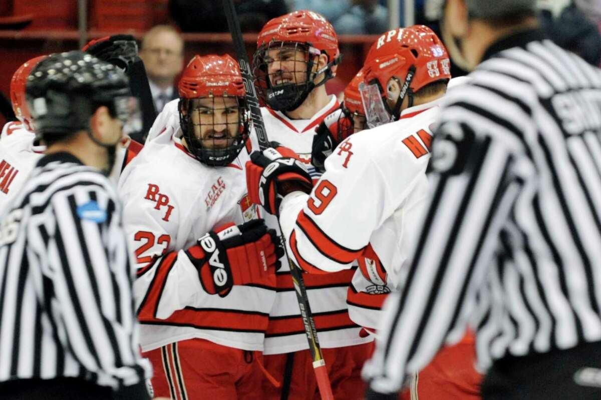 RPI's Brock Higgs, left, celebrates a first period goal with teammates during their hockey game against Denver on Friday, Dec. 13, 2013, at Rensselaer Polytechnic Institute in Troy, N.Y. (Cindy Schultz / Times Union)
