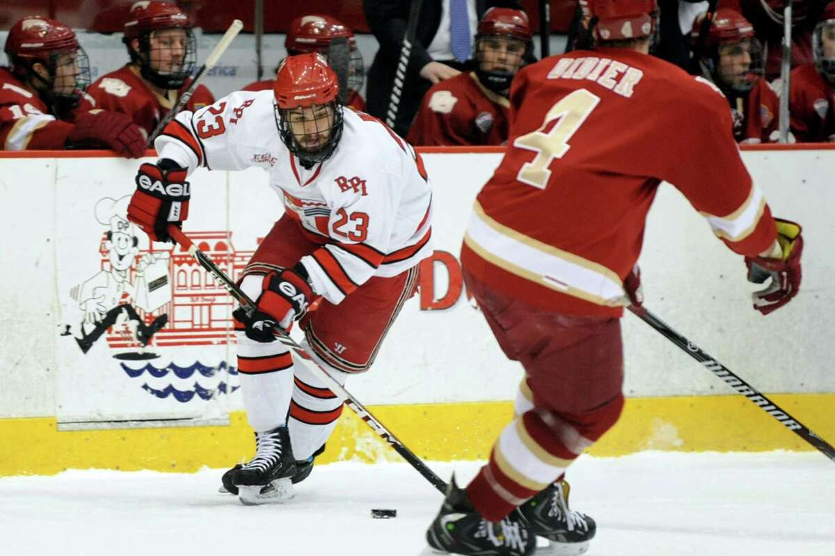 RPI's Brock Higgs, left, controls the puck as Denver's Josiah Didier defends during their hockey game on Friday, Dec. 13, 2013, at Rensselaer Polytechnic Institute in Troy, N.Y. (Cindy Schultz / Times Union)