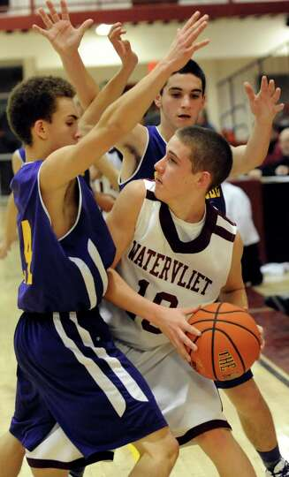 Watervliet's Danny Burns, center, looks to pass during their basketball game against Voorheesville o
