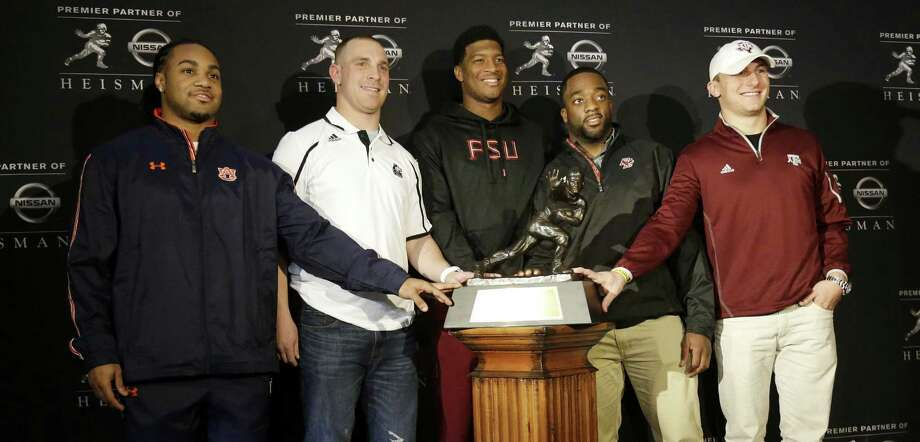 Cleared of sexual assault allegations, Florida State's Jameis Winston (center) is the overwhelming favorite to win the Heisman Trophy. Standing with Winston are Auburn's Tre Mason (from left), Northern Illinois' Jordan Lynch, Boston College's Andre Williams and A&M's Johnny Manziel, last year's Heisman winner. Photo: Julio Cortez / Associated Press / AP