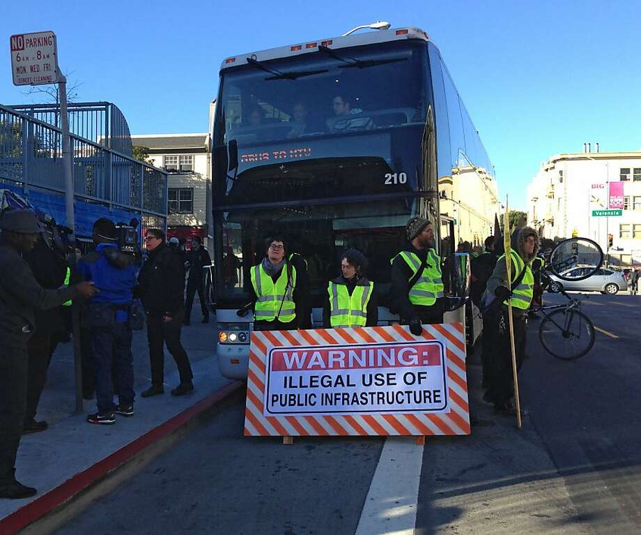 Protesters surround and block a Mountain View-bound Google employee commuter bus Monday morning at a Muni bus stop at 24th and Valencia streets in San Francisco's Mission District. The demonstration delayed the bus and its riders for about half an hour while protesters held up signs and chanted against private buses using Muni buses to pick up employees. Photo: Ellen Huet, The Chronicle