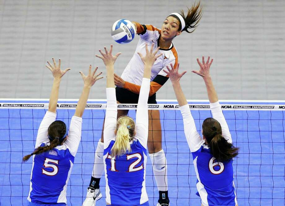 Texas' Haley Eckerman goes for a kill but is blocked by a trio of American players in NCAA volleyball play at Lincoln, Neb. The Longhorns won to advance. Photo: Nati Harnik, STF / AP