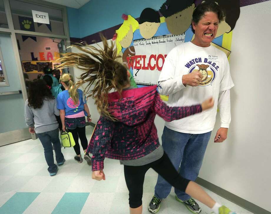 Watch DOGS member Mark Lunsford jokingly grimaces as he fist-bumps with a student at Stone Oak school. Photo: Bob Owen / San Antonio Express-News / © 2012 San Antonio Express-News