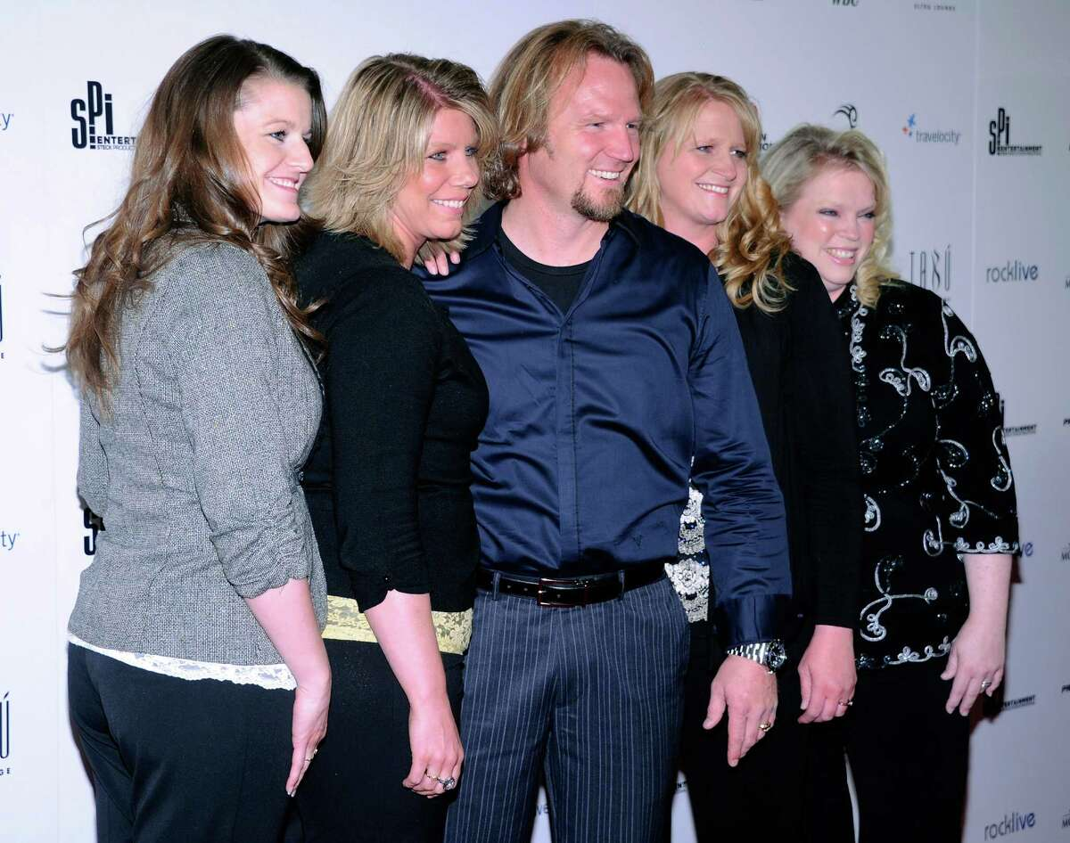 Polygamist Kody Brown, center, poses with his four wives at the opening of Mike Tyson's one-man show,