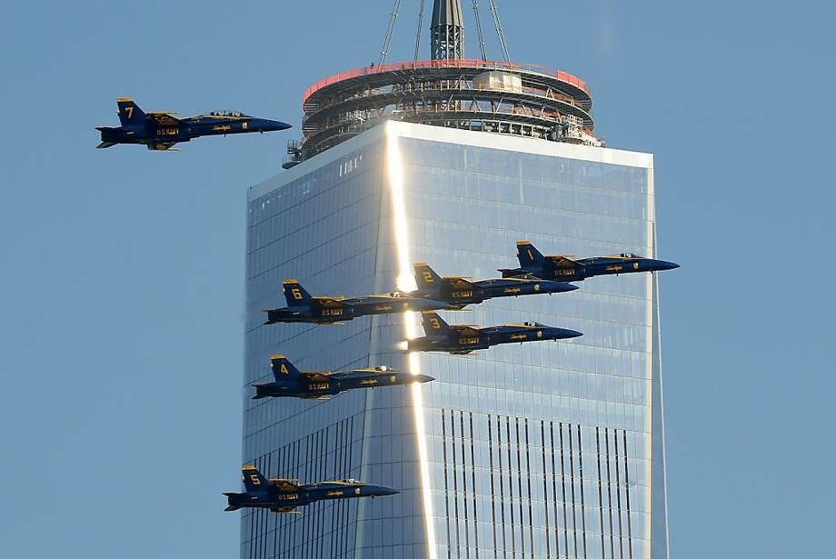 Six F/A-18 Hornets, members of the U.S. Navy's Blue Angels flight demonstration team, pass windows on One World Trade Center, Friday, Dec. 13, 2013 in New York. The Blue Angels return to the New York area for the 11th annual Bethpage Air Show at Jones Beach on Memorial Day weekend. (AP Photo/The Jersey Journal, Reena Rose Sibayan) Photo: Reena Rose Sibayan, Associated Press