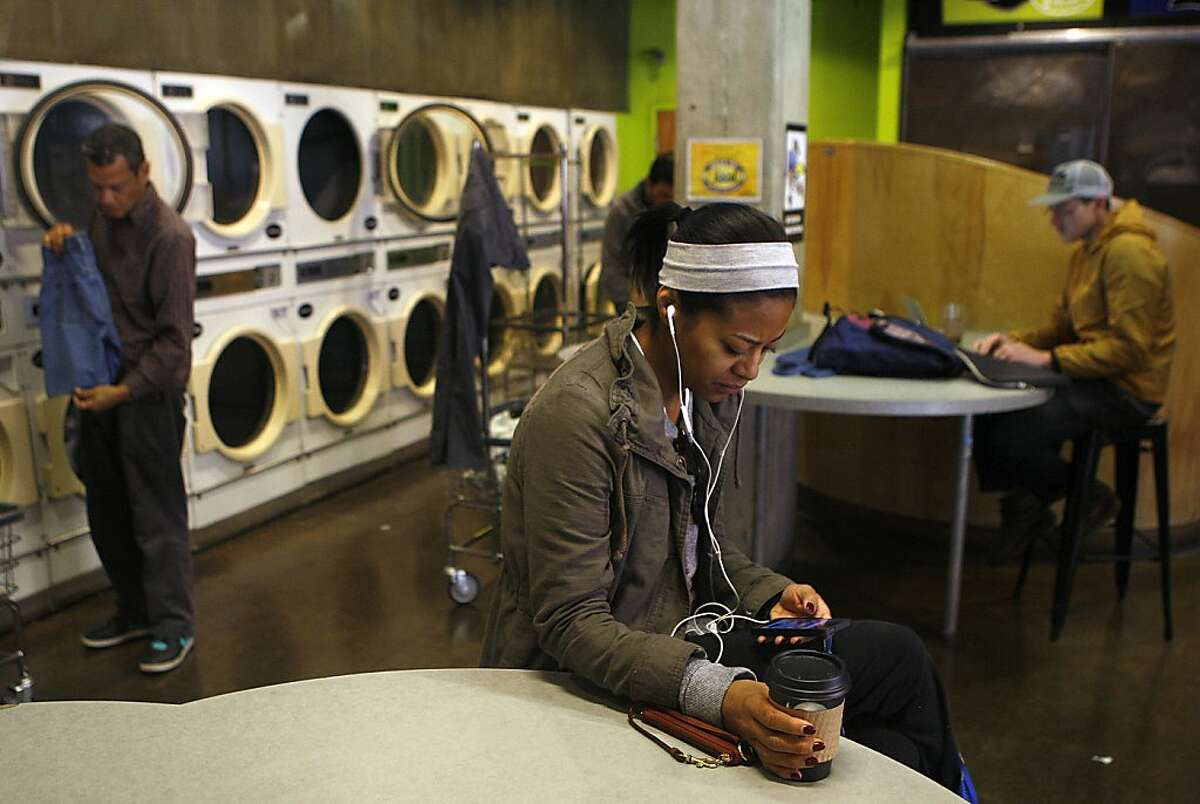 Nikkiya Carlos (front) on her phone while waiting for wash at Brainwash in San Francisco, Calif., on Thursday, December 5, 2013. She works in customer service and has lived in the SoMa for the past seven years. She said it seems like the new tech industry is mainly in the office for now.