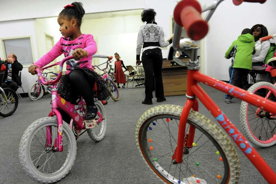 La'Viasia Smith, 5, left, rides her new bicycle from the Troy Bike Rescue on Saturday, Dec. 14, 2013, at the Troy Police North Station in Troy, N.Y. The Troy Bike Rescue had 60 second-hand bikes to give to children ages 12 and under. (Cindy Schultz / Times Union) Photo: Cindy Schultz / 00024939A