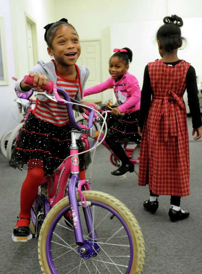 Lataysha Smith, 7, and her sister La'Viasia Smith, 5, center, ride new bicycle from the Troy Bike Rescue on Saturday, Dec. 14, 2013, at the Troy Police North Station in Troy, N.Y. At right is Nicaiha Furman, 5. The Troy Bike Rescue had 60 second-hand bikes to give to children ages 12 and under. (Cindy Schultz / Times Union) Photo: Cindy Schultz / 00024939A
