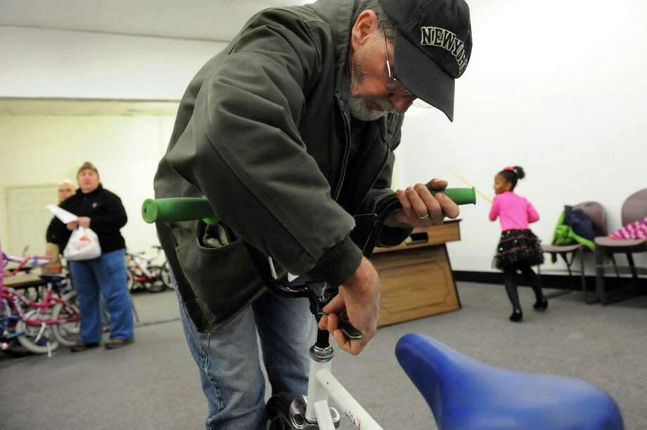 Mike Rozdolski, volunteer and board member of the Troy Bike Rescue, tightens handle bars on a bike on Saturday, Dec. 14, 2013, at the Troy Police North Station in Troy, N.Y. (Cindy Schultz / Times Union) Photo: Cindy Schultz / 00024939A