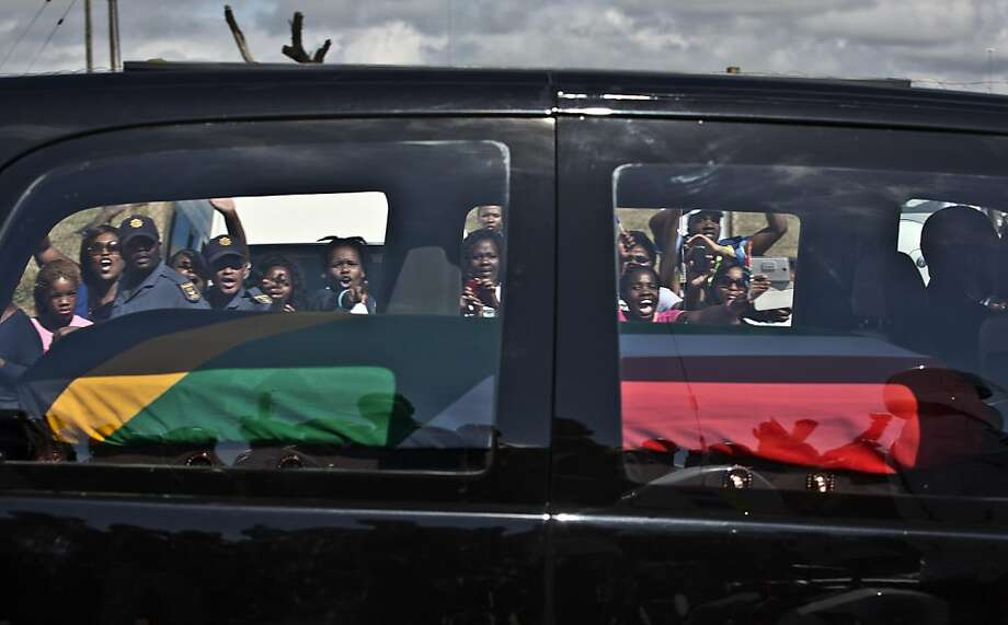 South African mourners wave and cheer as the hearse transporting the body of Former President Nelson Mandela passes through the town of Mthatha on its way to Qunu, South Africa, Saturday, Dec. 14, 2013. (AP Photo/Muhammed Muheisen) Photo: Muhammed Muheisen, Associated Press