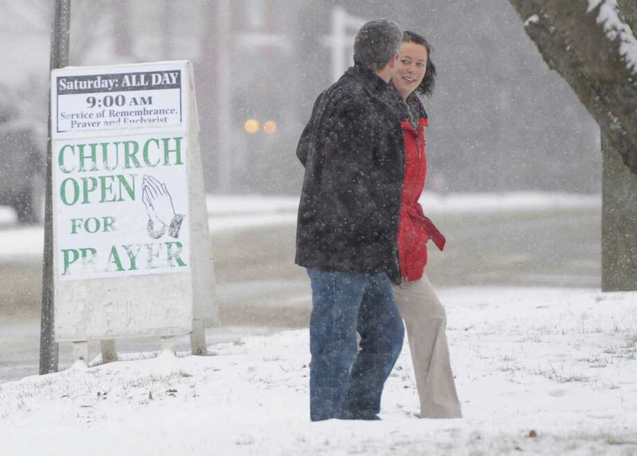 Churchgoers walk to Trinity Church in Newtown, Conn. on Saturday, Dec. 14, 2013, the one-year anniversary of the Sandy Hook Elementary School shooting that killed 26 students and educators.  The church held a special remembrance service at 9 a.m. with open prayer throughout the day.  Snow fell on the town Saturday, casting a somber mood as residents remembered the tragedy one year ago. Photo: Tyler Sizemore / The News-Times
