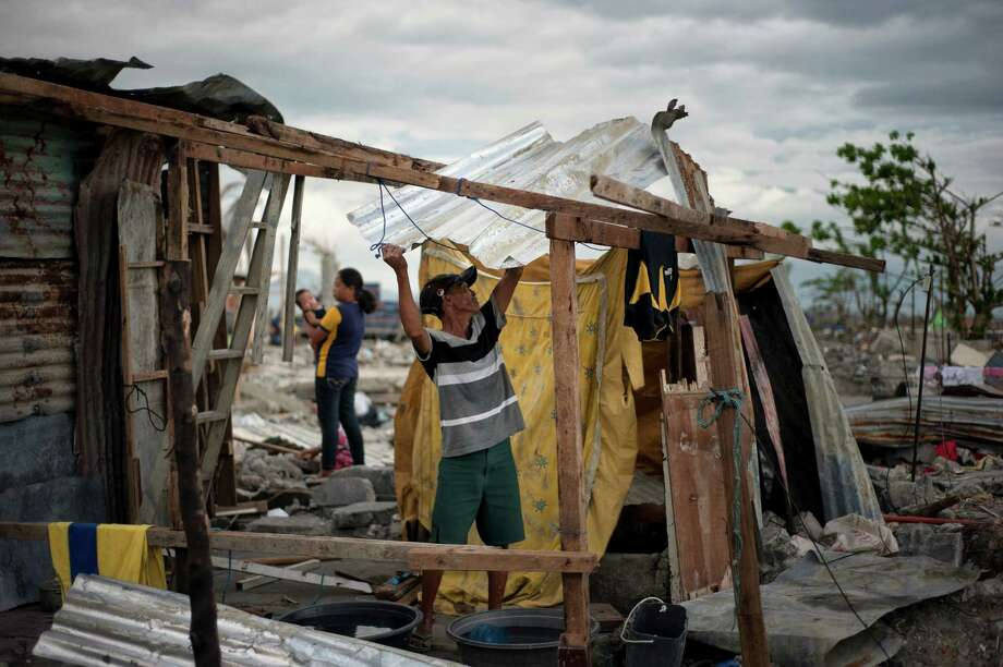 A man erects a makeshift house in Barangay, a small village in Tacloban, Philippines. The Romualdez clan of former first lady Imelda Marcos and squatters are waging a land battle after a typhoon ripped the area. Photo: JES AZNAR, STR / NYTNS