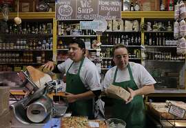 Juan Carnejo (left) and Vince Balistreri serve customers during the busy lunch hour at Molinari Delicatessen in the North Beach neighborhood of San Francisco, Calif. on Thursday, Dec. 12, 2013.