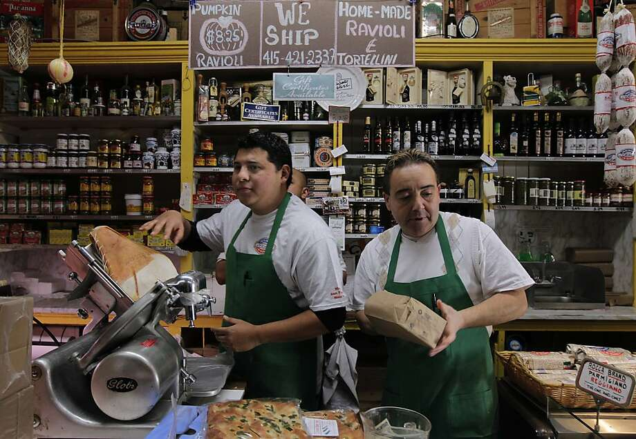 Juan Carnejo (left) and Vince Balistreri serve lunch customers at Molinari Delicatessen in North Beach. Photo: Paul Chinn, The Chronicle