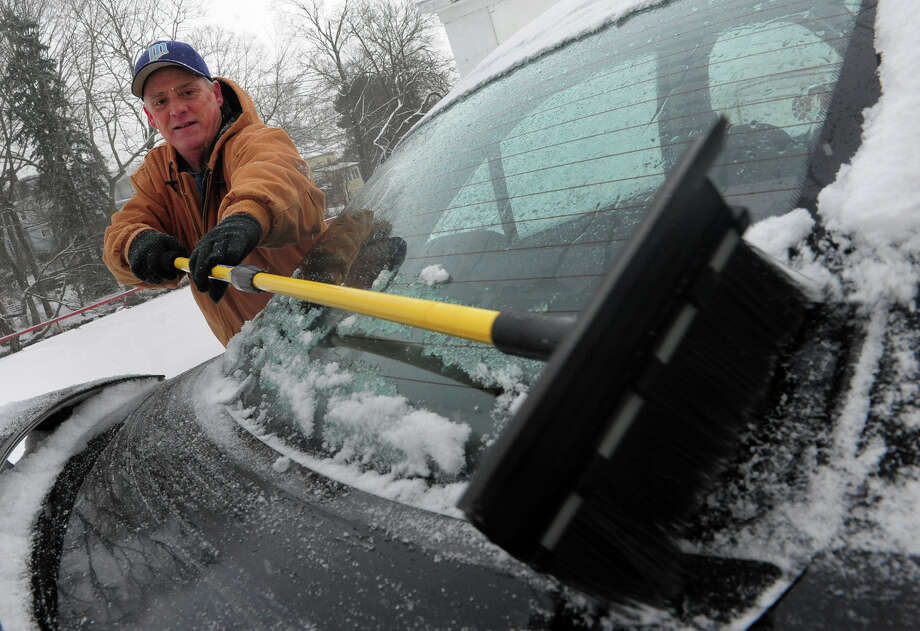 Dave Quinn gets the snow off of his son's car during the snow storm in Milford, Conn. on Saturday December 14, 2013. Photo: Christian Abraham / Connecticut Post