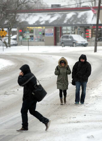 Elizabeth Nelson, of NYC, center, and her friend Aaron Javian, at right, make their way along River Street during the snow storm in Milford, Conn. on Saturday December 14, 2013. Photo: Christian Abraham / Connecticut Post