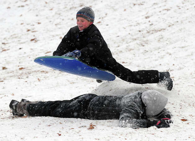Parker Matthews, 9, flies over his brother Andrew, while sledding during the snow storm in Stratford, Conn. on Saturday December 14, 2013. Photo: Christian Abraham / Connecticut Post
