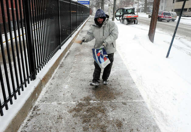 Bridgeport Hospital employee Carlos Perez, spreads rock salt onto the sidewalk during the snow storm on Mill Hill Avenue in Bridgeport, Conn. on Saturday December 14, 2013. Photo: Christian Abraham / Connecticut Post