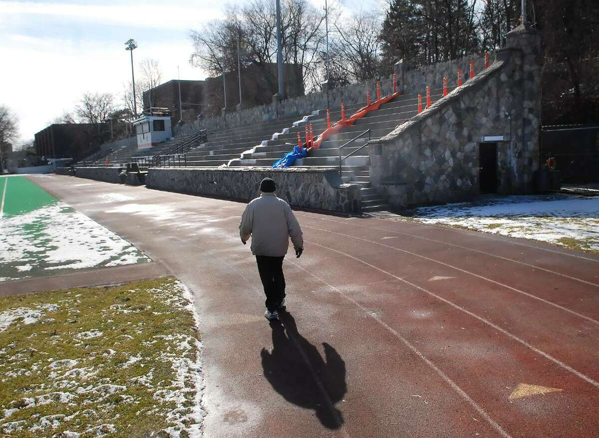 A Stamford senior citizen, who would not give his name but said he did not understand why the Boyle Stadium renovation was taking so long, walks the track at the stadium Monday afternoon, Feb. lst, 2010. At right the bleachers at the northwestern end of the stadium remain off-limits to the public.