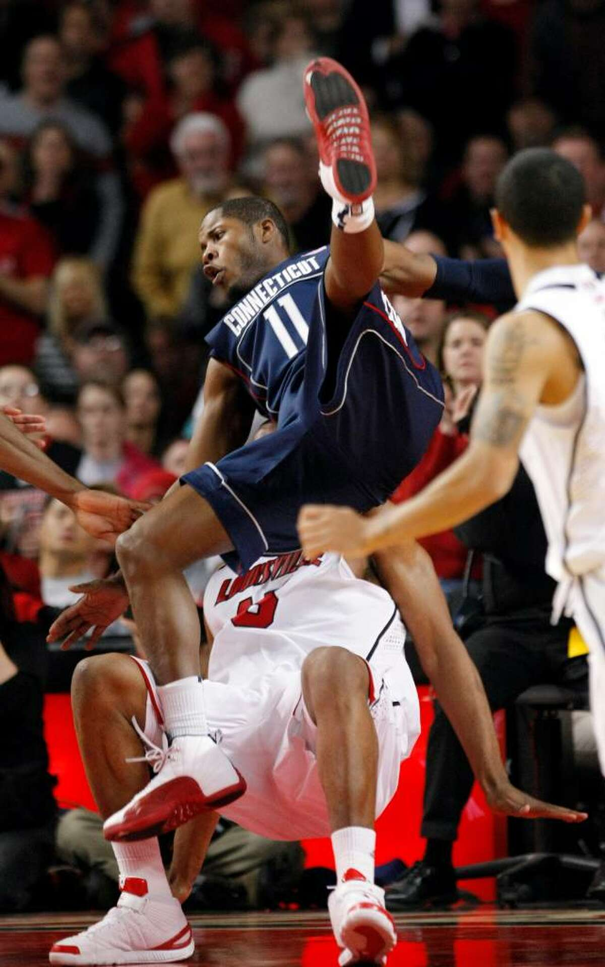 Connecticut's Jerome Dyson charges into Louisville's Samardo Samuels during the second half of an NCAA college basketball game in Louisville, Ky., Monday, Feb. 1, 2010. Dyson led all scorers with 18 points in the 82-69 Louisville win. (AP Photo/Ed Reinke)