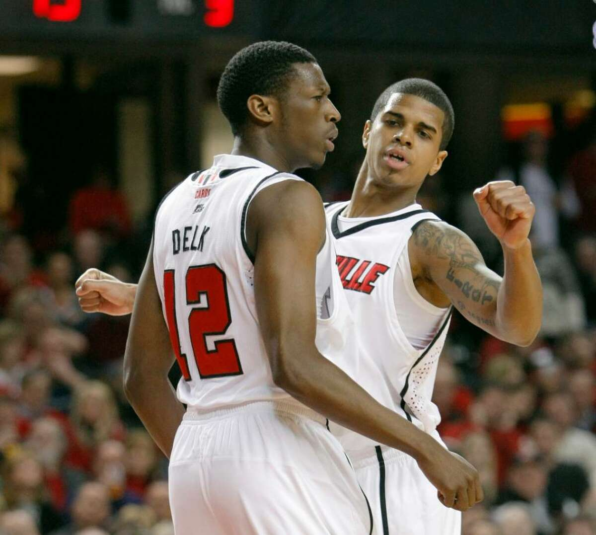 Louisville's Edgar Sosa, right, chest bumps teammate Reginald Delk during the second half of an NCAA college basketball game in Louisville, Ky., Monday, Feb. 1, 2010. Sosa scored 15 points and handed out eight assists in the 82-69 Louisville win. (AP Photo/Ed Reinke)
