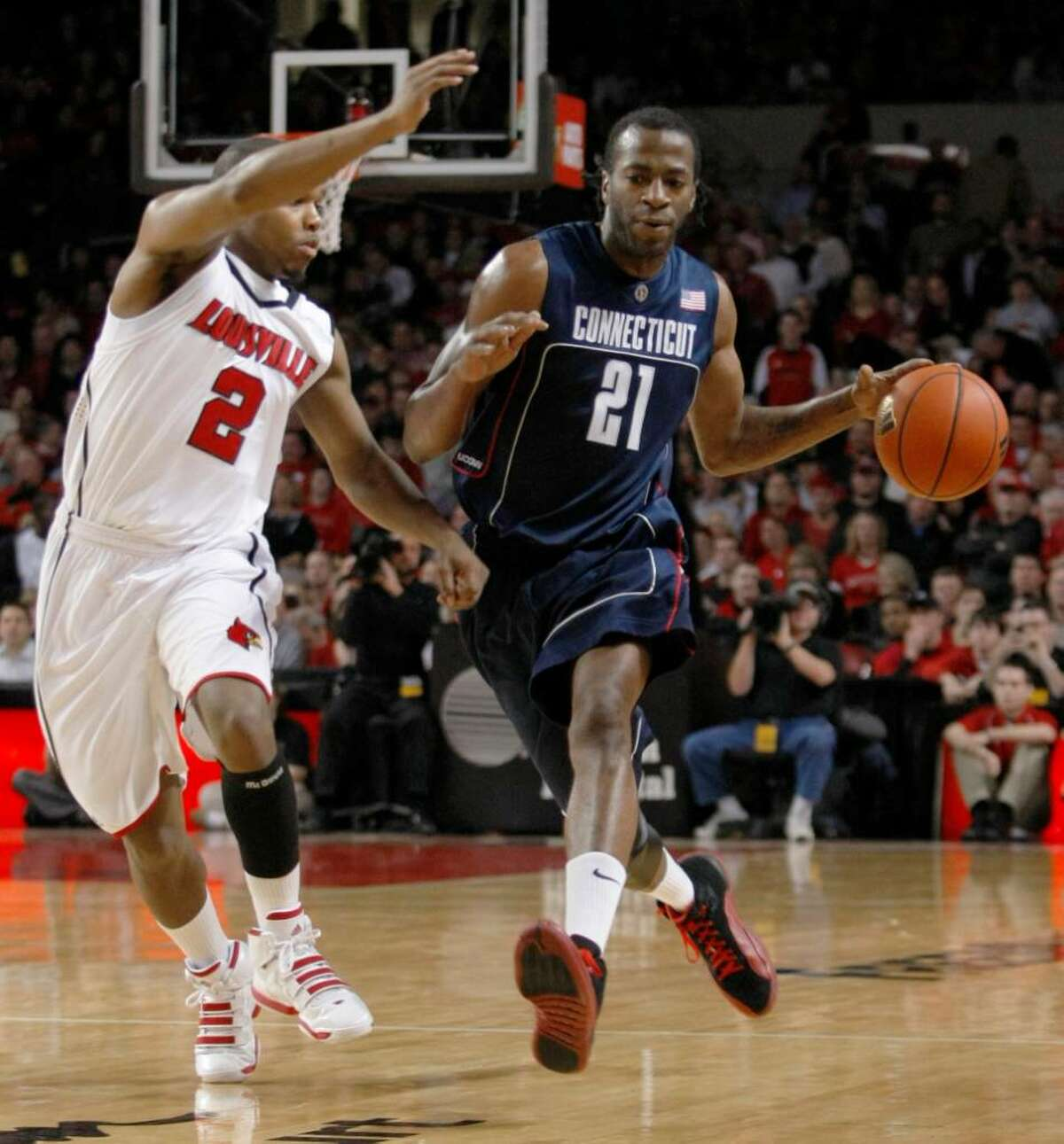 Connecticut's Stanley Robinson drives past Louisville's Preston Knowles during the first half of an NCAA college basketball game in Louisville, Ky., Monday, Feb. 1, 2010. (AP Photo/Ed Reinke)