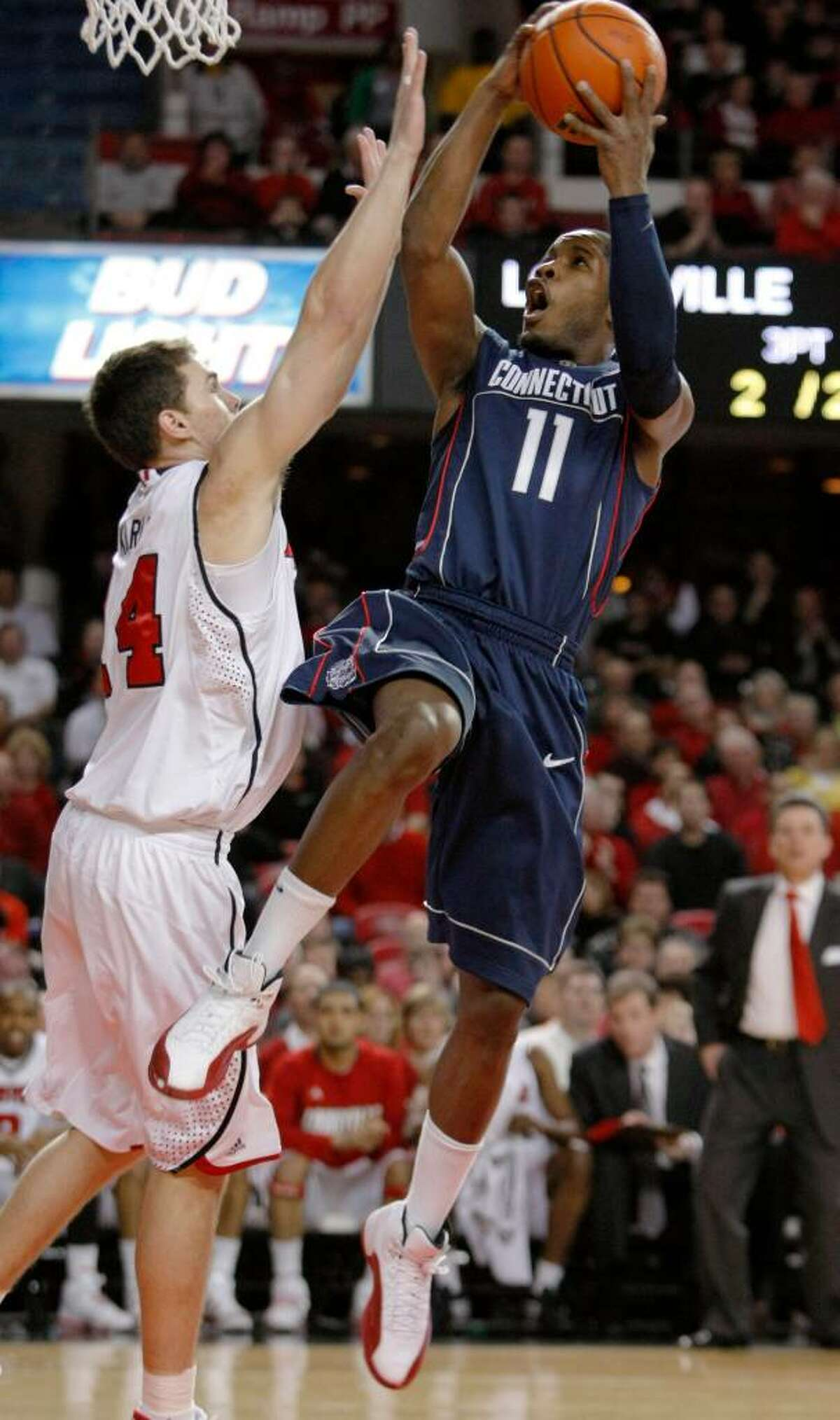 Connecticut's Jerome Dyson shoots over Louisville's Kyle Kuric during the first half of an NCAA college basketball game in Louisville, Ky., Monday, Feb. 1, 2010. (AP Photo/Ed Reinke)