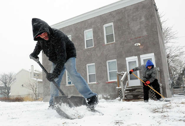 Jose Gonzelez shovels snow at an apartment building during the snow storm on Barnum Avenue in Bridgeport, Conn. on Saturday December 14, 2013. Helping in back is his friend Anibao Marrero. Photo: Christian Abraham / Connecticut Post