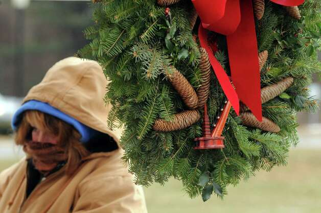 Dawn Foglia of Wild Things Rescue Nursery from Valley Falls keeps bundled up as she sells Christmas wreaths outside during the Saratoga Springs indoor farmer's market at SPA State Park on Saturday Dec. 14, 2013 in Saratoga , N.Y. (Michael P. Farrell/Times Union) Photo: Michael P. Farrell / 00025043A