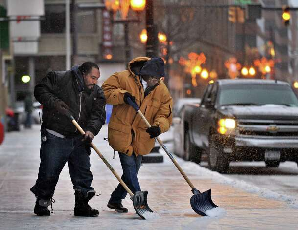 Roy Isaac, left, and Ronald Meadows of the Times Union Center operations crew work to keep up with the snowfall on the sidewalks outside the Center Saturday Dec. 14, 2013, in Albany, NY.  (John Carl D'Annibale / Times Union) Photo: John Carl D'Annibale / 00025043A