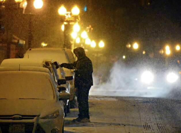 A motorist cleans snow off his car on South Pearl Street as a steady snow falls Saturday evening Dec. 14, 2013, in Albany, NY.  (John Carl D'Annibale / Times Union) Photo: John Carl D'Annibale / 00025043A