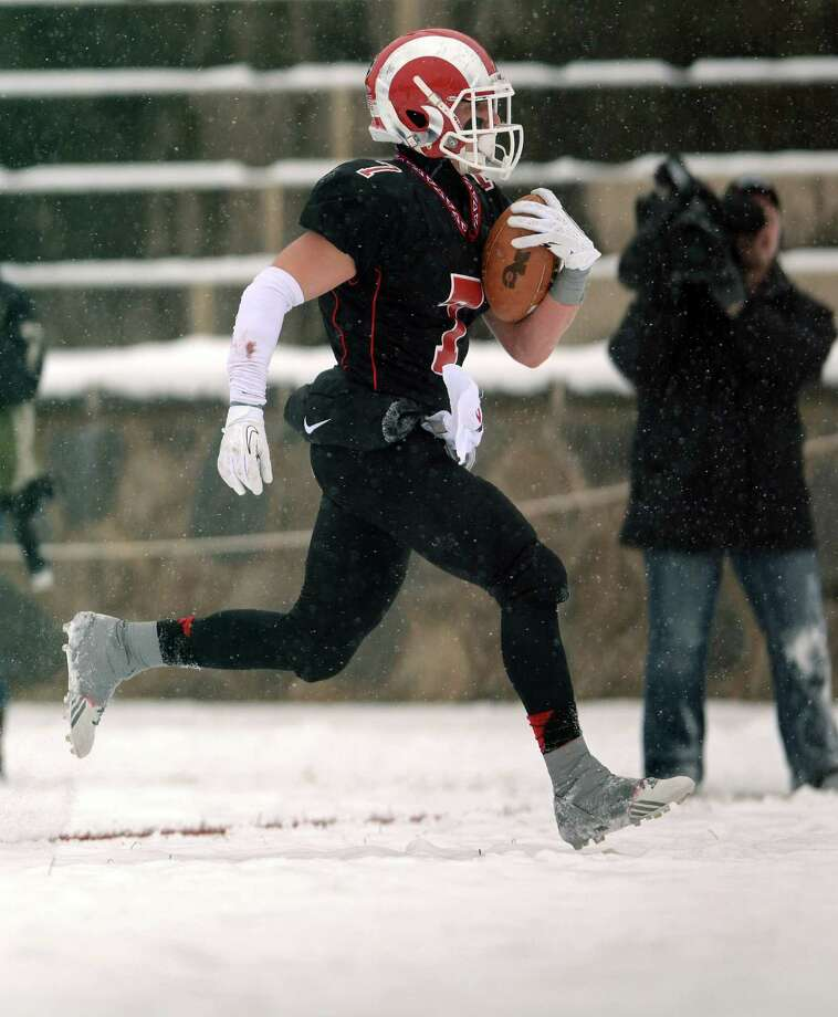 Alex LaPolice seemed to be built for the snow. The New Canaan senior set  the tone of the game by returning the opening kick-off 61 yards,  putting the Rams in great field position. Photo: Autumn Driscoll / Connecticut Post